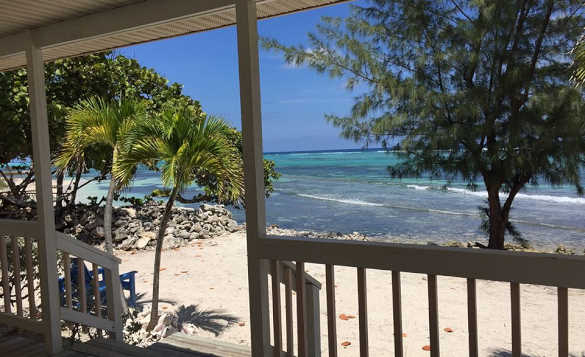 View from a wooden veranda to the Caribbean Sea lapping against a sandy beach/