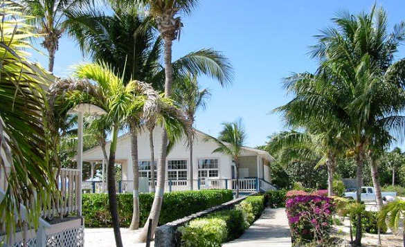 White bungalow with palm trees located at Paradise Villas, Little Cayman/