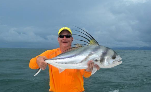 Angler holding a large rooster fish/