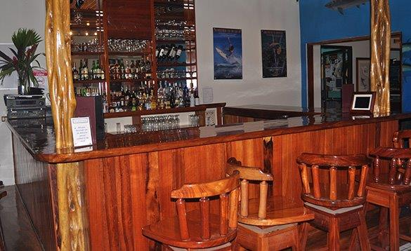 Well stocked bar with wooden high stools around the counter/