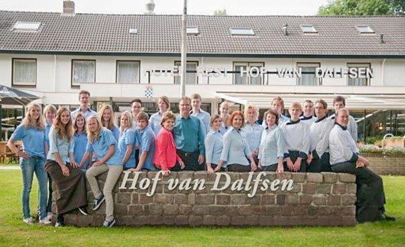 large group of people standing in front of a hotel and behind a small stone wall with Hof van Dalfsen in white lettering on it/