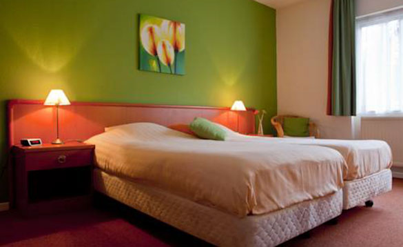 hotel bedroom with double bed and two lights lit on the bedside cabinets/