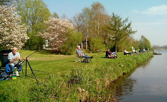 Group of anglers sat fishing on a grassy bank beside a canal in Holland/