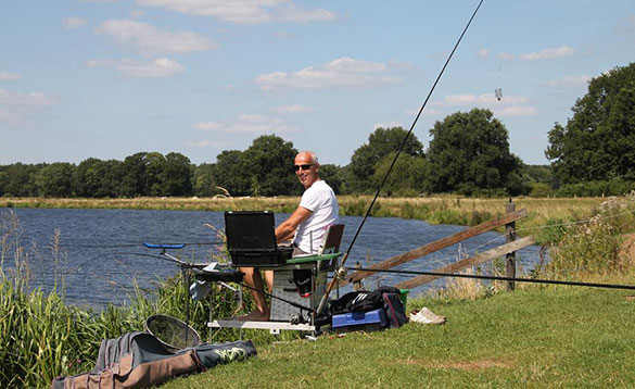 Angler sat on a tackle box on a grassy bank beside a reed fringed canal in Holland/