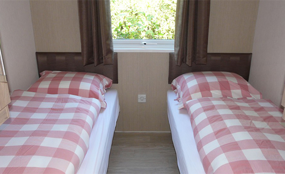 Bedroom with two single beds in a Comfort Chalet at De Visotter holiday park/