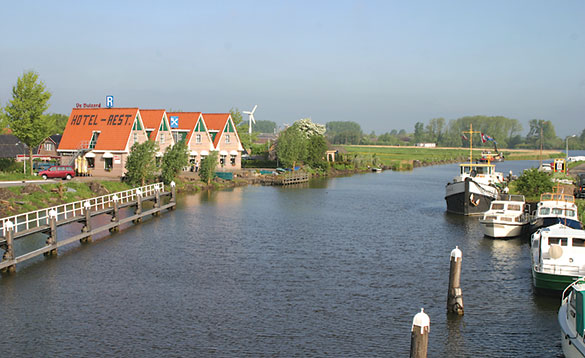 view of a canal with boats moored on the right and a hotel on the left/