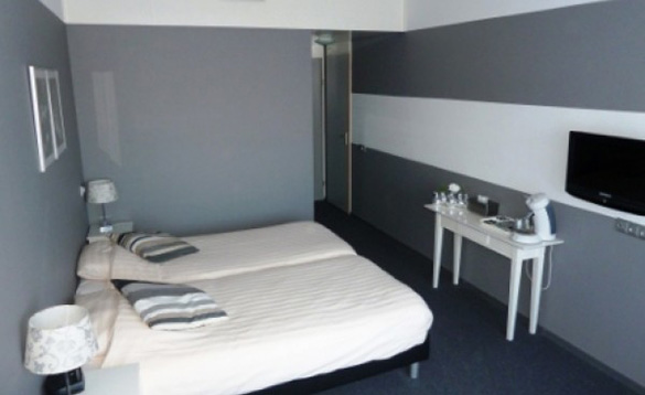 Bedroom in the Hotel Molengroet with two single beds and grey painted walls/
