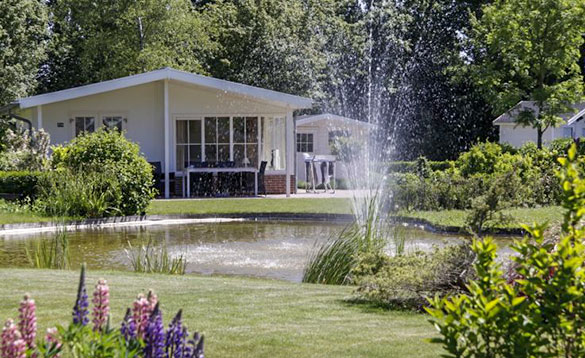 view over a pond with a fountain to a white chalet surrounded by lawns and flower beds/