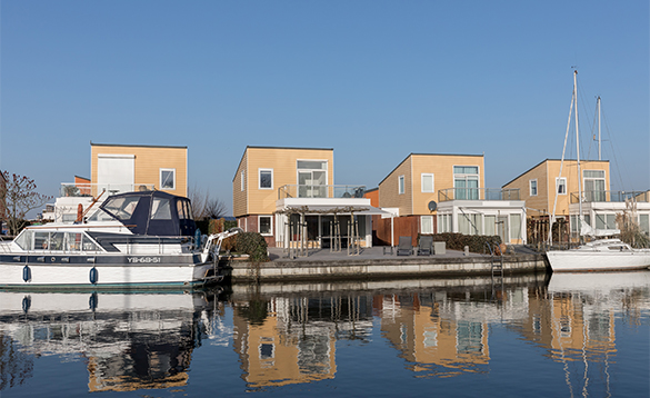 Boats moored outside villas at Nautic Rentals, Oude Tonge/
