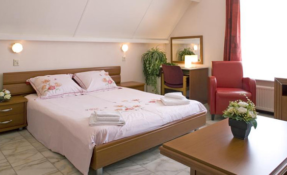hotel bedroom with tiled floor, red leather chair and double bed with pink bed linen/