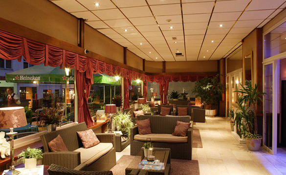 large conservatory attached to a hotel with wicker sofas and chairs, pot plants and red swagged curtains/