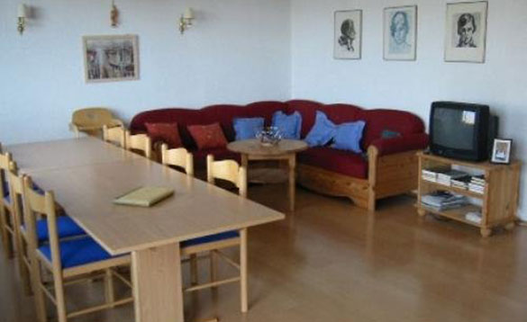 living/dining room with large red corner sofa and pine table with six chairs/