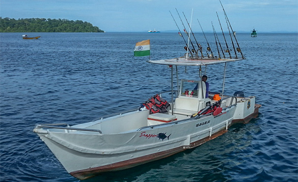 Man driving a fishing boat through calm waters in the Andaman Islands/