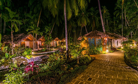 Paved walkway leading through palm trees past the cabins at the Munjoh Ocean Resort/