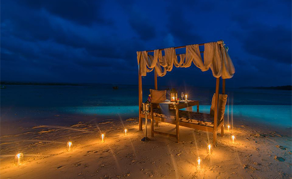 Lighted candles leading down a beach to a table set for an evening meal beside the sea/