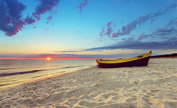 Boat on a white sandy beach /