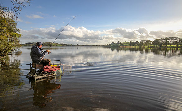 angler sitting on a tackle box in the shallow water at the edge of a river fishing/