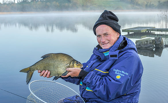 angler holding a recently caught bream /