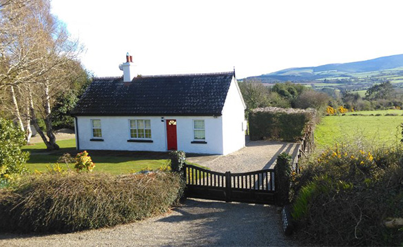 Traditional white Irish cottage with mountains in the background/