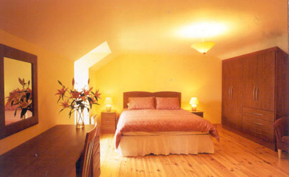 yellow painted bedroom with double bed and dark wooden wardrobe/