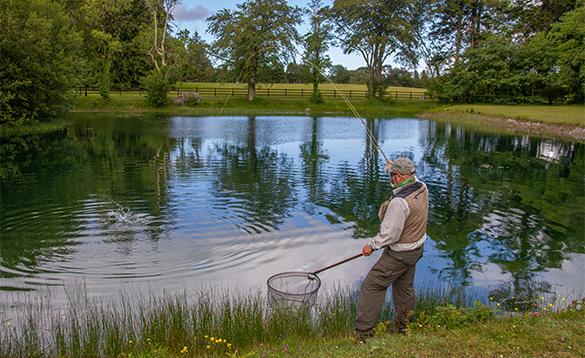 Angler fishing on a lake at Mount Falcon in Co Mayo, Ireland/