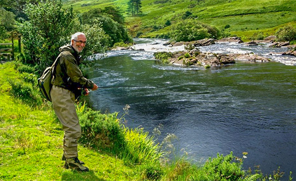 Angler stood on a grassy bank fishing in a river in Ireland/
