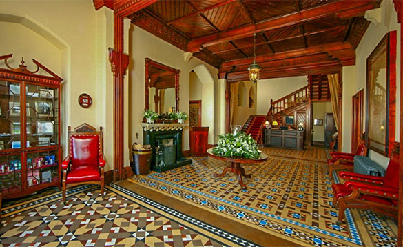Entrance hall at the Mount Falcon Hotel with brightly coloured tiled floors and luxurious red leather armchairs/