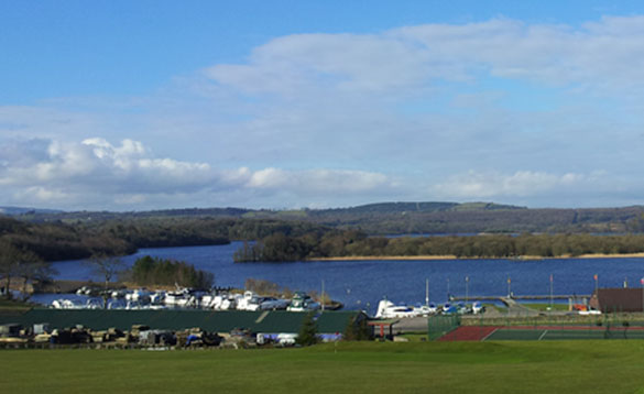view across a field to a large lough with an island in the middle and boats moored in a marina in the foreground/