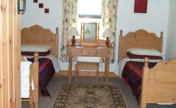 Bedroom with two pine single beds and pine dressing table in Cornode self-catering in Ireland/