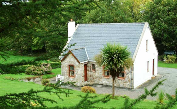 Cornode self-catering a white painted stone fronted cottage surrounded by lawns and trees/