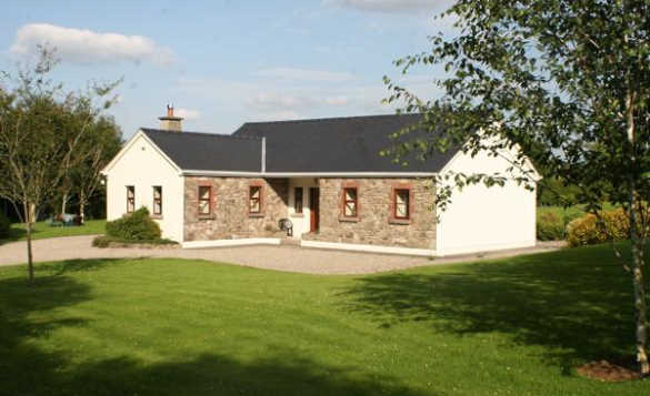 White painted stone front bungalow of Fraoch self-catering cottage in Ireland/