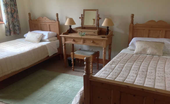 Bedroom at Froach self-catering cottage with two pine single beds and pine dressing table/