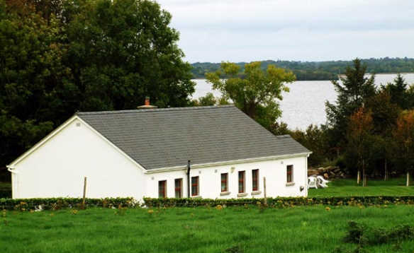 White painted single storey cottage of Fraoch self-catering with views over Lough Derg in Ireland/