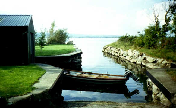 Rowing boat with outboard motor in a private harbour leading out onto Lough Derg in Ireland/