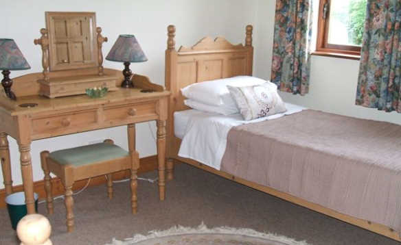 Bedroom at Fraoch self-catering with pine single bed and dressing table/