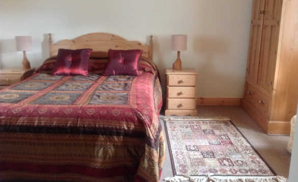 Bedroom at Lackaroe self-catering with pine double bed, bedside cabinets and wardrobe/