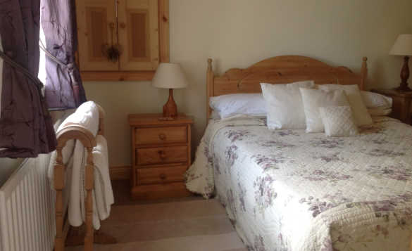 Bedroom at Lackaroe self-catering cottage with pine double bed and bedside cabinets/