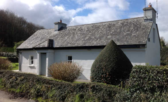 White painted Irish cottage with grey slate roof/