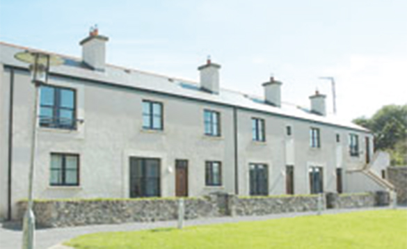 row of four terraced houses painted white with stone wall in front/