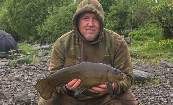 Angler holding a tench caught in Ireland/
