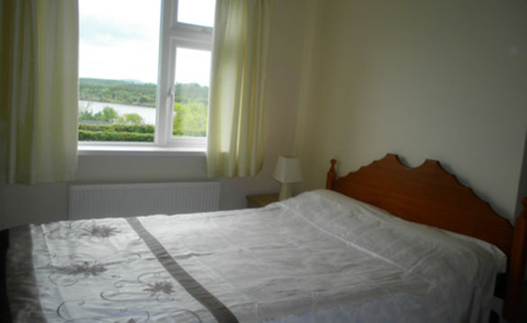 pine double bed with white bed linen placed near to a window with views of a lake surrounded by trees/