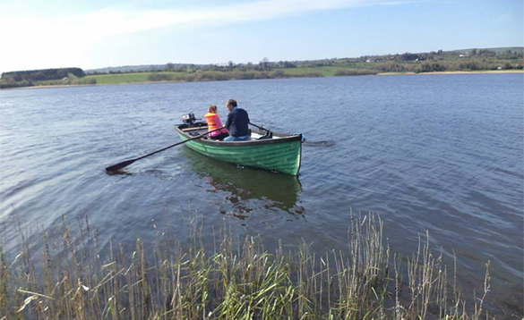 Man and a child on a green rowing boat on a lake in Ireland/