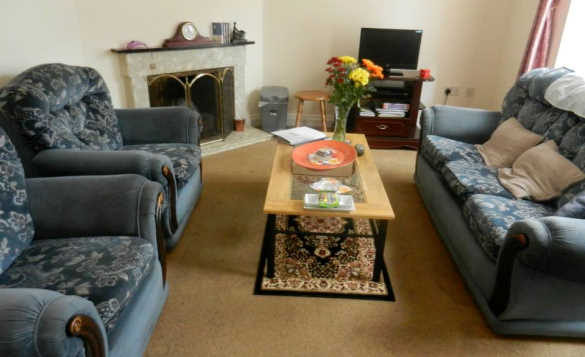 Lounge with blue three piece settee in the self-catering property of Erneside Townhouses, Belturbet/
