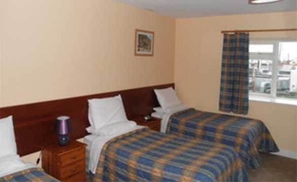 Bedroom with three single beds at Fitzpatricks Tavern, Lough Gowna/