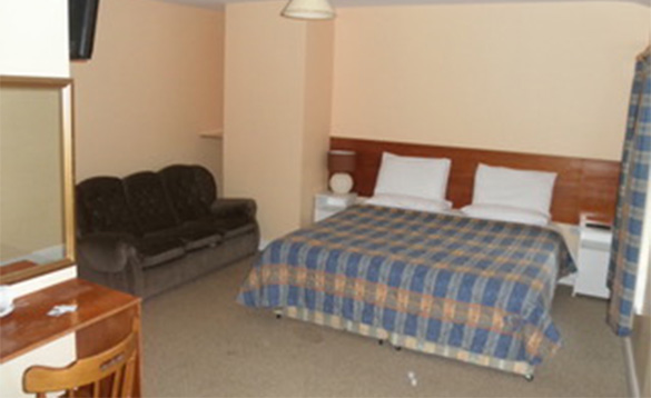 Bedroom at Fitzpatricks Tavern, Lough Gowna with double bed and sofa/