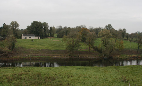 View across fields towards the River Erne and a bungalow located amongst trees up a small hill/