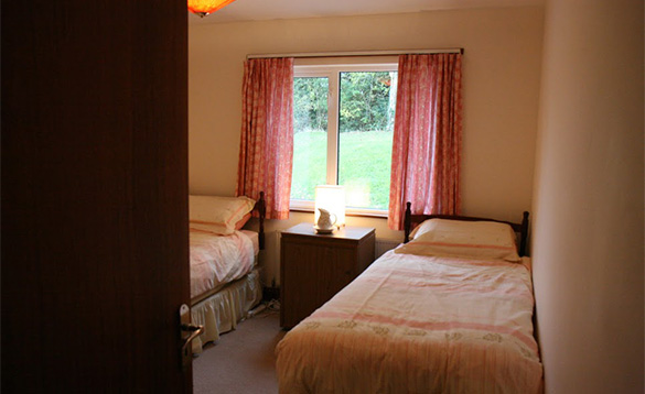 Bedroom with two single beds at Magee Lodge/