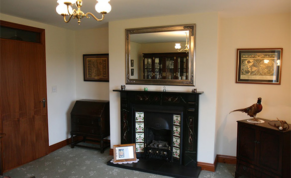 Mirror over a cast iron fireplace in the living room of Magee Lodge/