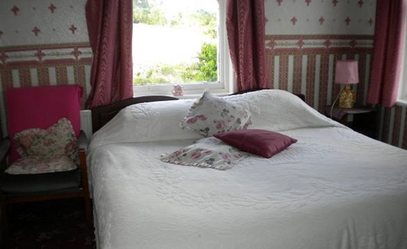 double bed under a window with white bed linen and pink flower pattened cushions on it/