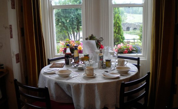 dining table seating four laid for breakfast situated in a bay window with views over gardens and a stone bridge over a river/